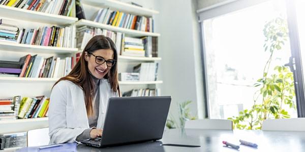 Mujer joven leyendo un ebook en una biblioteca virtual