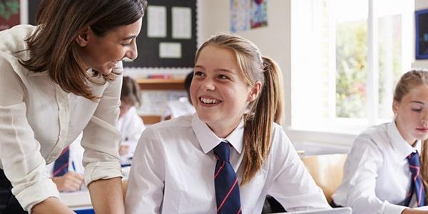 Maestra con alumna en un aula de escuela privada