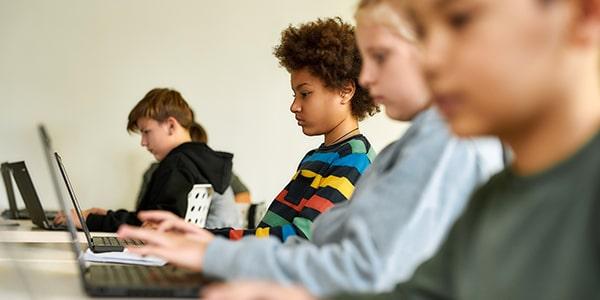 Grupo de niños trabajando con plataformas digitales en computadoras