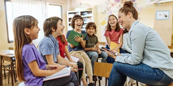 Grupo de niños con una maestro en un aula de escuela primaria