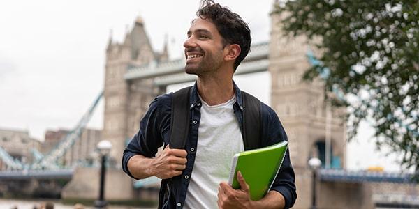 Hombre joven con libros en la mano en Londres