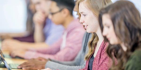 Grupo de adolescentes realizando pruebas de inglés a través de una computadora