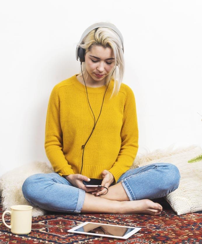 Mujer joven sentada en el piso leyendo desde un teléfono móvil